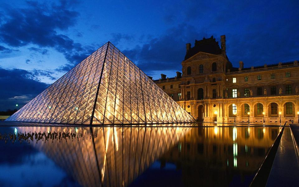 Una foto di notte del celebre museo a forma di piramide e della piazza entrambi illuminati da tante lampadine