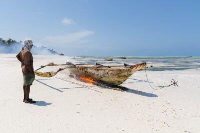 Plage de Pingwe : pêcheur qui nettoie son bateau